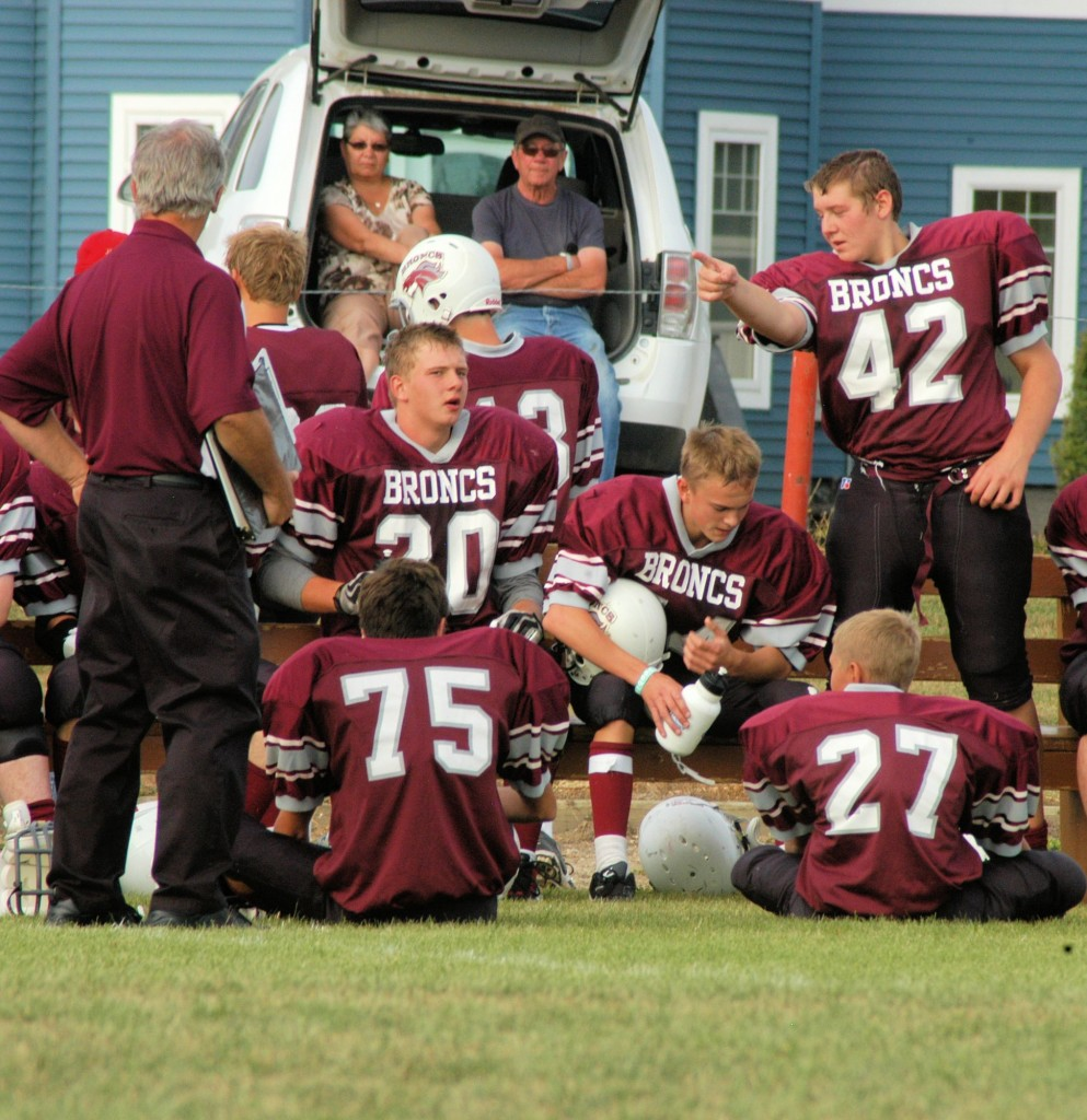 The 2013 edition of the McLurg Broncs football team takes a halftime break during a home game. McLurg is also home to basketball, volleyball, track and badminton teams, as well as a provincially competitive wrestling team.