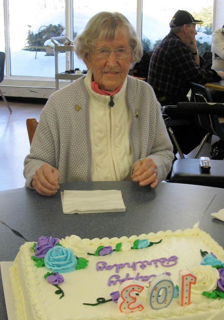 Barbara Risling poses with her birthday cake at a tea celebrating her 103rd birthday.